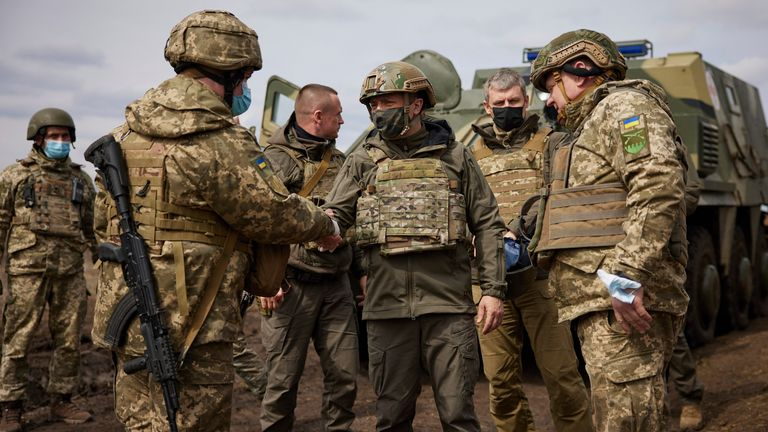 Ukrainian President Volodymyr Zelenskiy shakes hands with a soldier as he visits the war-hit Donetsk region, eastern Ukraine, Thursday, April 8, 2021. Ukraine's president is visiting the area of conflict in his country's east amid an escalation of tensions that has raised fears of a resumption of large-scale hostilities. (Ukrainian Presidential Press Office via AP)