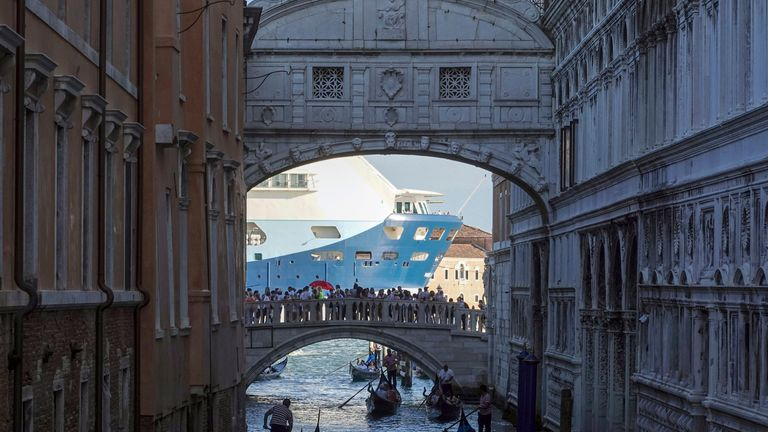 A cruise ship passes the Bridge of Sighs as it leaves Venice