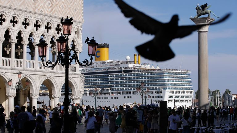 A cruise ship passes by St. Mark's Square filled with tourists, in Venice