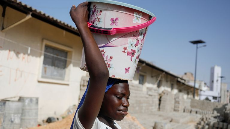 A girl carries a bucket of clean water in Pikine on the outskirt of Dakar, Senegal March 9, 2020. Picture taken March 9, 2020. REUTERS/Zohra Bensemra