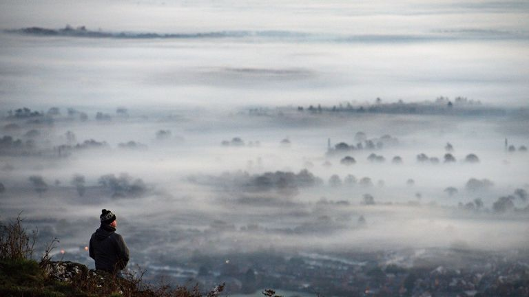A walker observes the fog and mist at dawn from the Malvern Hills looking over Worcestershire.