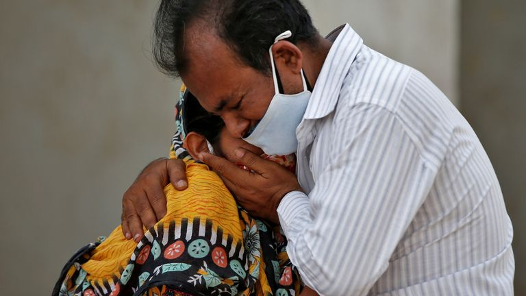 A woman is consoled by her relative after her husband died from COVID-19 outside a COVID-19 hospital in Ahmedabad, India