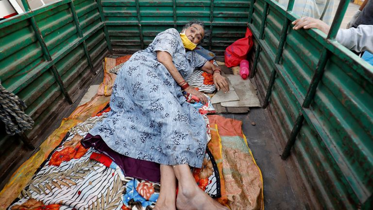 A woman lies in the back of a load carrier also waiting to enter a hospital, in Ahmedabad. Pic: Reuters