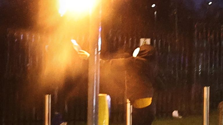 A youth throws a petrol bomb at some traffic lights on the Springfield road, during further unrest in Belfast. Picture date: Thursday April 8, 2021.