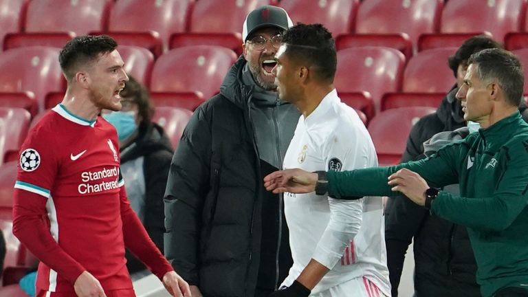 Liverpool's manager Jurgen Klopp, background, yells as Liverpool's Andrew Robertson, left, argues with Real Madrid's Casemiro