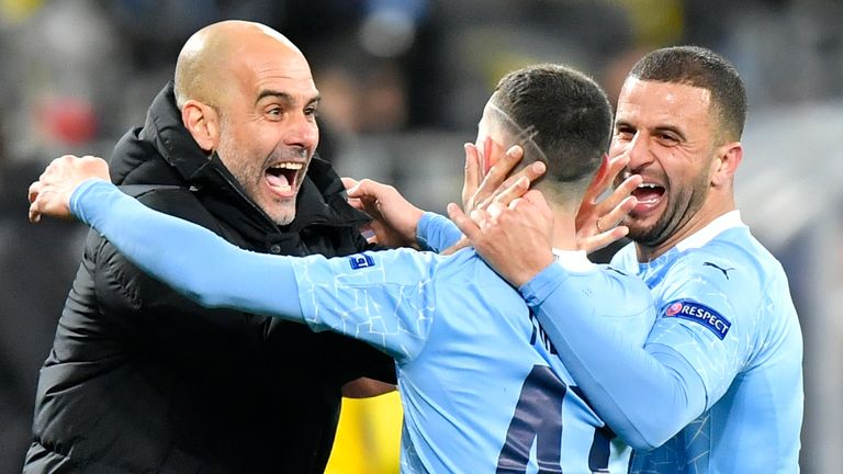 Manchester City's head coach Pep Guardiola celebrates with goal scorer Manchester City's Phil Foden during the Champions League quarterfinal second leg soccer match between Borussia Dortmund and Manchester City at the Signal Iduna Park stadium in Dortmund
