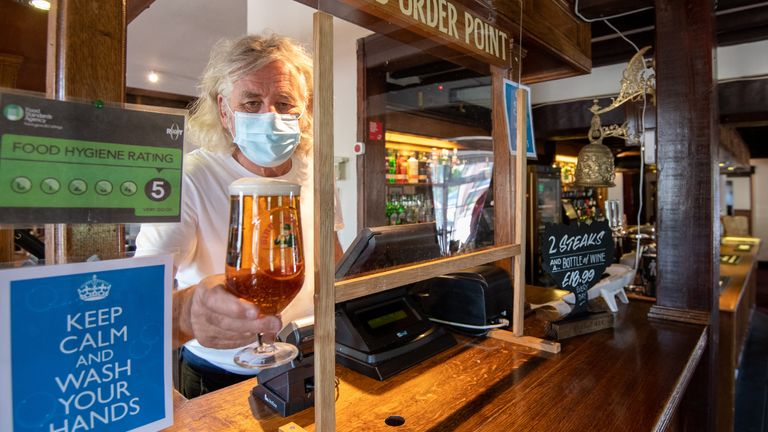 "Phil Weaver, owner of The Old Smithy pub in Church Lawford, Warwickshire holds a pint of beer from behind a protective screen, as pub and hospitality bosses have cheered the Government's proposals to allow customers through their doors again on July 4 as ""a welcome relief""."
