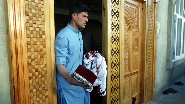 Мужчина держит окровавленный тюрбан и кепку после взрыва Фото: AP