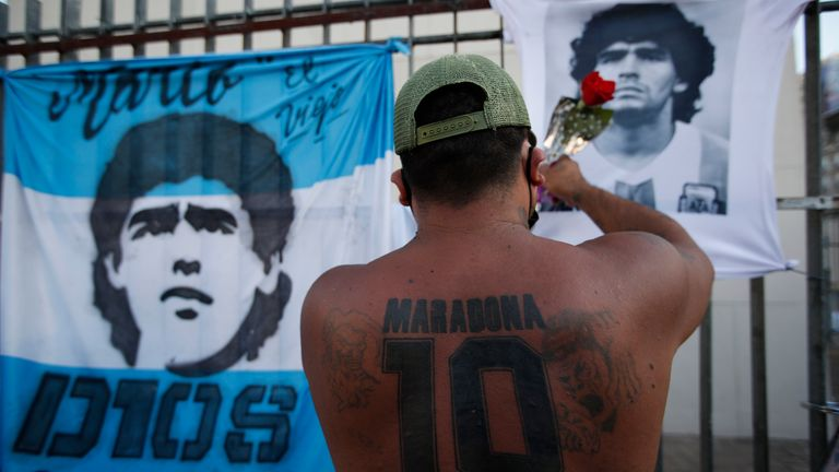 A soccer fan places a flower on a jersey with the face of late soccer star Diego Maradona during a march to demand answers regarding his death, in Buenos Aires, Argentina, Wednesday, March 10, 2021. An investigation was opened into the circumstances surrounding Maradona's death after he passed away last November. (AP Photo/Natacha Pisarenko)