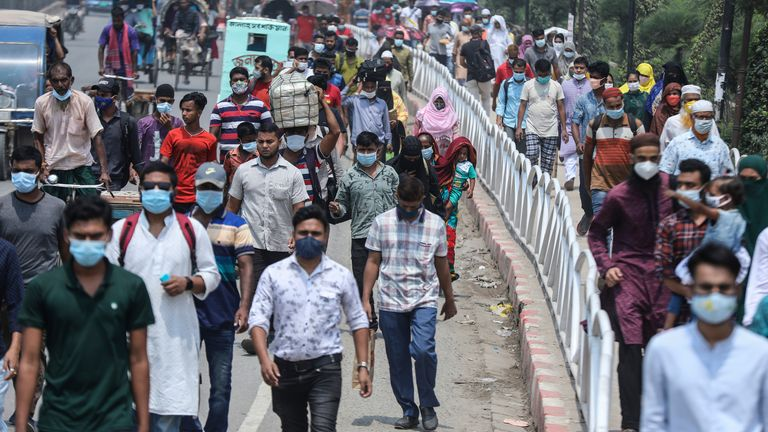 People wearing face masks a precaution against the coronavirus leave the city to travel to their native places ahead of Eid al-Fitr in Dhaka, Bangladesh