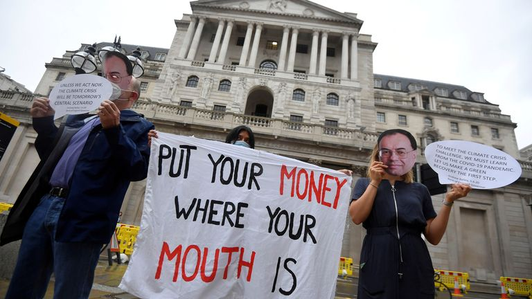 Environmental activists wear face masks depicting the governor of the Bank of England, Andrew Bailey, during a protest to encourage a green economy, outside of the Bank of England in the City of London, Britain, August 6, 2020