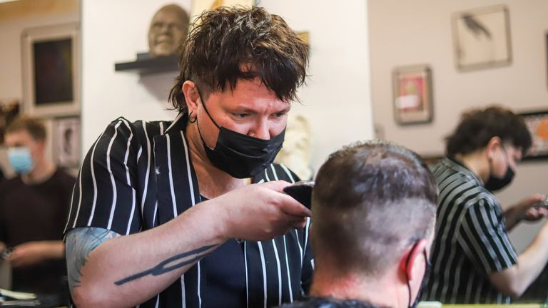 Barbershop owner Aidan Coogan with a client at the ÔNeighbourhood ThreatÕ barber shop in Dublin