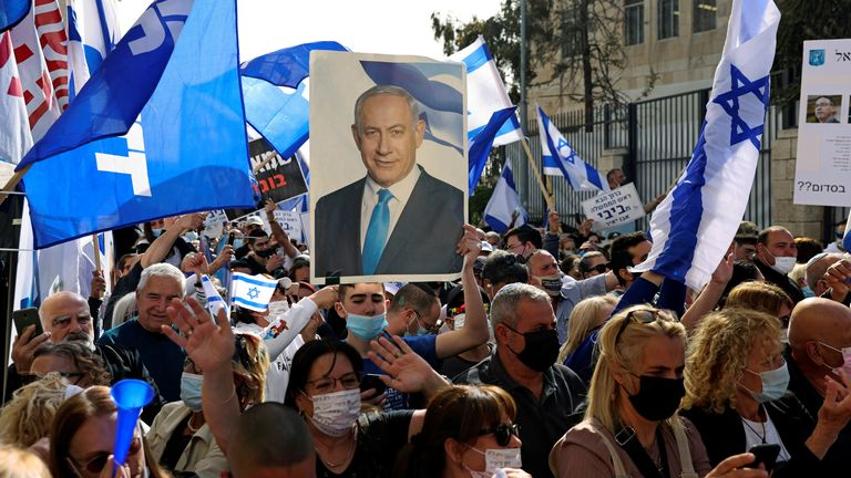 Supporters of Israeli Prime Minister Benjamin Netanyahu, wave flags and hold a placard depicting Netanyahu, during a rally as Netanyahu's corruption trial resumes, near Jerusalem's District Court April 5, 2021. REUTERS/Ronen Zvulun