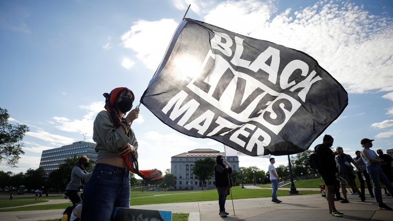 Cecilia Lopez, from Wisconsin, holds a Black Lives Matter flag