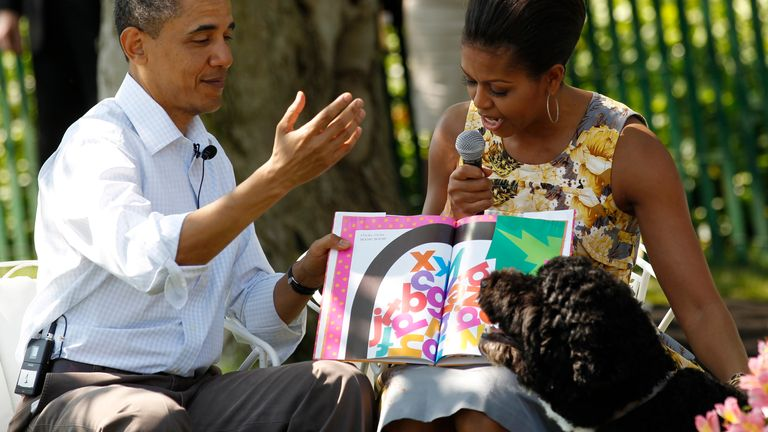 """U.S. President Barack Obama reacts to their dog Bo (bottom) as first lady Michelle Obama (R) reads a book titled """"Chicka Chicka Boom Boom"""" to children during the annual Easter Egg Roll, at the White House in Washington April 25, 2011"""