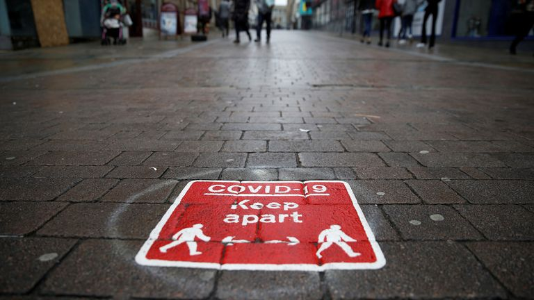 People walk past a social distancing marker following the outbreak of the coronavirus disease (COVID-19) in Bolton,