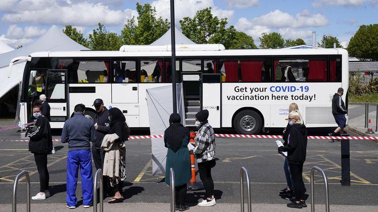 مردم برای واکسیناسیون COVID که در اتوبوس بولتون انجام می شود در صف هستند
