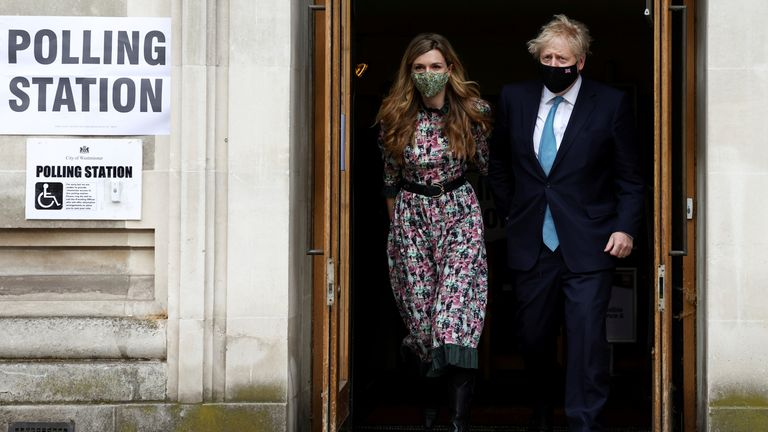 Britain's Prime Minister Boris Johnson and partner Carrie Symonds leave Westminster polling station after voting, in London, Britain May 6, 2021. REUTERS/Henry Nicholls