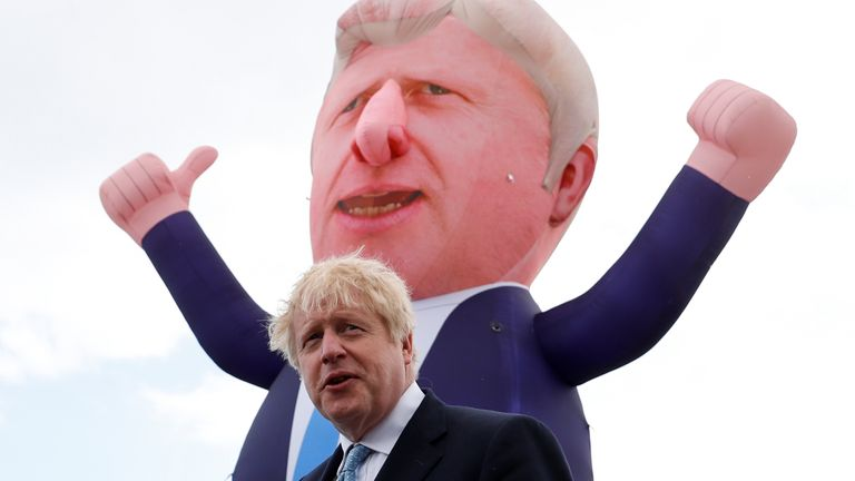 Prime Minister Boris Johnson speaks, with an inflatable figure depicting him in the background, at Jacksons Wharf Marina in Hartlepool following local elections