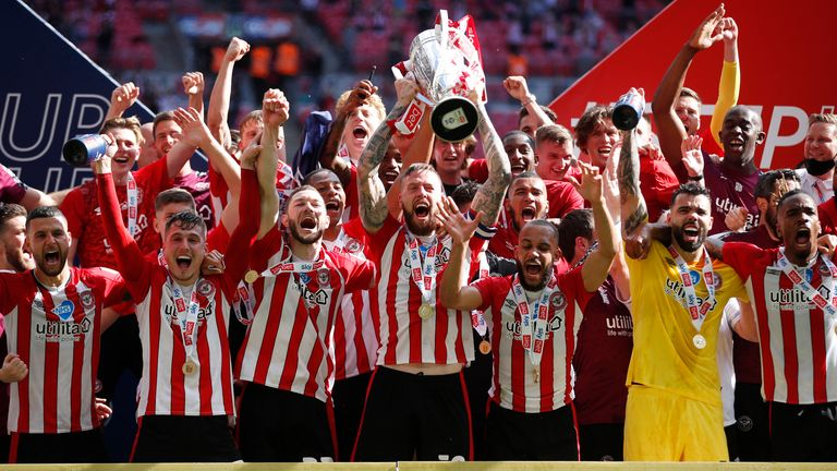 Brentford captain Pontus Jansson (C) lifts the trophy as they celebrate after winning Championship play-off final