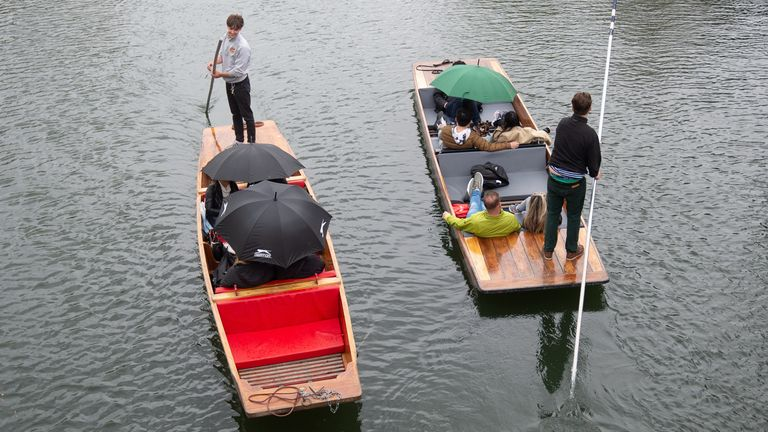 People shelter under umbrellas while punting along the River Cam in Cambridge as the unsettled conditions move across the country