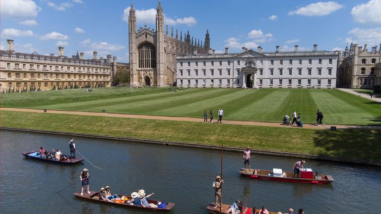 People enjoy punt tours past King's College on River Cam in Cambridge