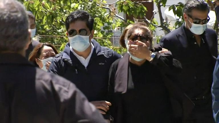 Mourners are pictured wearing masks to the service