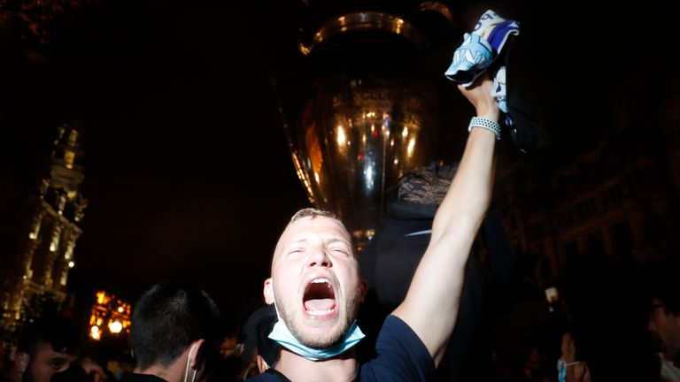 Fans celebrate in front of an inflatable trophy