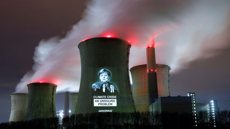 Greenpeace activists project images of German Chancellor Angela Merkel (top), German Economy minister Peter Altmaier, SPD chairwoman Andrea Nahles and German Transport minister Andreas Scheuer (L-R) with a slogan onto a cooling tower of the brown coal power plant of RWE, one of Europe's biggest utilities in Neurath, north-west of Cologne, Germany, December 14, 2018. REUTERS/Wolfgang Rattay TPX IMAGES OF THE DAY