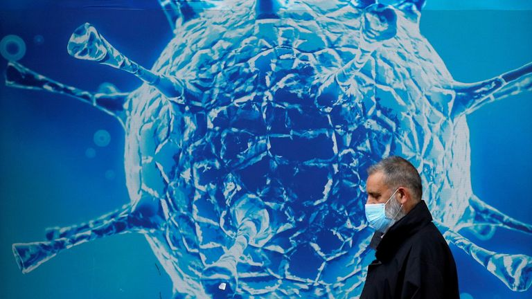A man wearing a protective face mask walks past an illustration of a virus outside a regional science centre amid the coronavirus disease (COVID-19) outbreak, in Oldham, Britain August 3, 2020