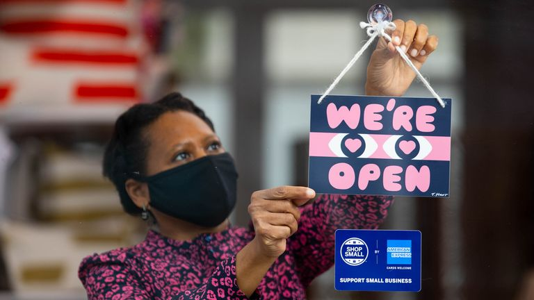 "Owner Isatu Funna from Dar Leone displays a ""we're open"" sign designed by artist Timothy Hunt, which has been created as part of the American Express Shop Small campaign and to help welcome people back to our high streets"