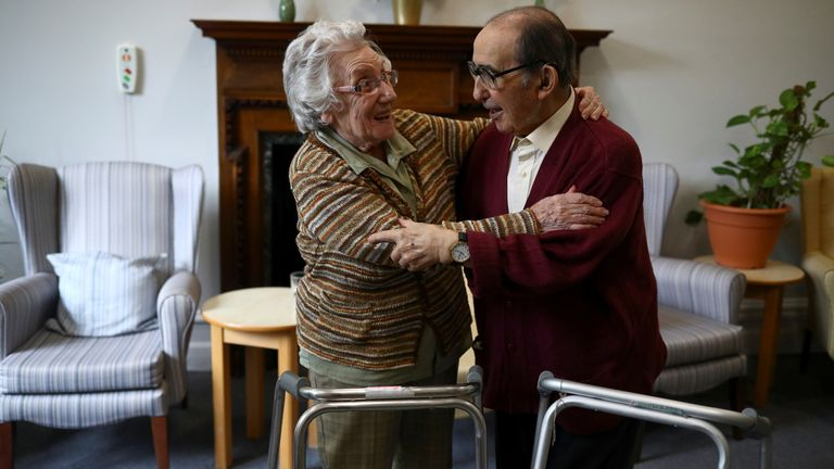 Residents Susan Crowe, 96, and Antonio Hernandez, 82, have a hug at Alexander House Care Home in Wimbledon