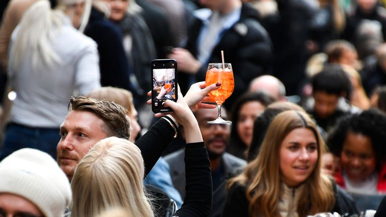 "A woman take a phone picture of her drink in Soho, in London, on the day some of England's third coronavirus lockdown restrictions were eased by the British government, Monday, April 12, 2021. People across England flocked to shed shaggy locks and browse for clothes, books and other ""non-essential"" items as shops, gyms, hairdressers, restaurant patios and beer gardens reopened Monday after months of lockdown. (AP Photo/Alberto Pezzali)"