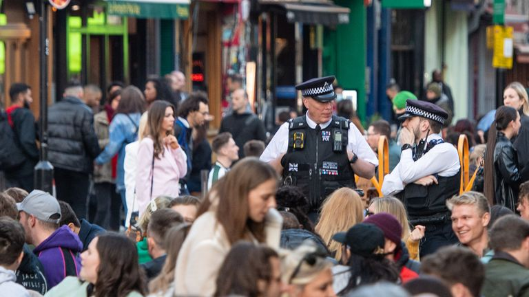 Police watch people eating and drinking at outside tables on Saturday evening in Soho, central London, following the further easing of lockdown restrictions in England. Picture date: Saturday April 24, 2021.