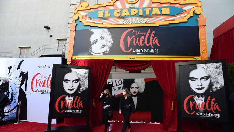 """Staff wearing masks appear on the red carpet before the premiere of """"Cruella"""" at the El Capitan Theatre on Tuesday, May 18, 2021, in Los Angeles. (Photo by Jordan Strauss/Invision/AP)"""