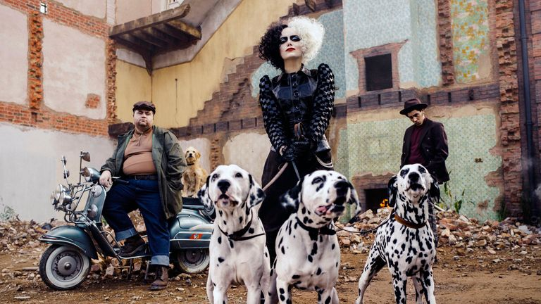"""This image released by Disney shows Paul Walter Hauser, from left, Emma Stone and Joel Fry in a scene from """"Cruella."""" (Disney via AP)"""