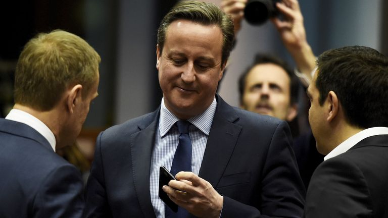 British Prime Minister David Cameron (C) checks his phones as he chats with Greek Prime Minister Alexis Tsipras (R) and European Council President Donald Tusk during a European Union leaders summit, addressing the talks about the so-called Brexit and the migrants crisis, in Brussels, Belgium, February 18, 2016. REUTERS/Dylan Martin