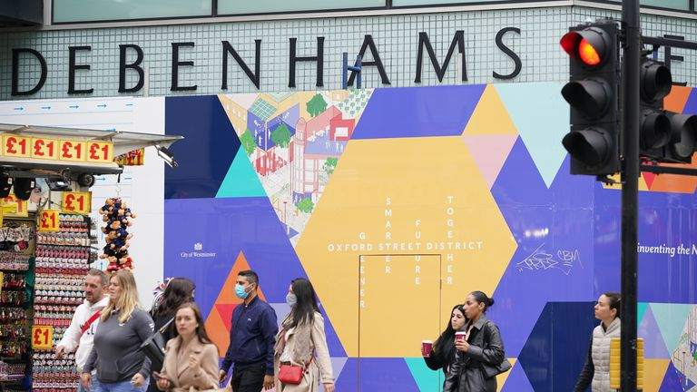 People walk past the boarded up former Debenhams flag-ship store in Oxford Street, London. Debenhams is to shut its doors for the final time in its 243-year history. The historic department store chain will close its remaining 28 stores across the UK for good on Saturday after the company collapsed amid the fallout of the coronavirus pandemic. Picture date: Friday May 14, 2021.
