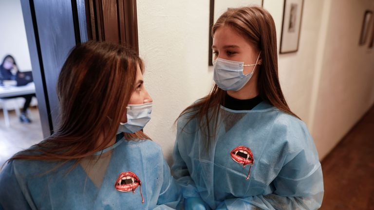Medical workers, wearing protective gowns decorated with bloody vampire mouth stickers, wait for patients at the temporary coronavirus disease (COVID-19) vaccination center at Bran Castle, in Brasov county, Romania, May 8, 2021. Inquam Photos/George Calin via REUTERS ATTENTION EDITORS - THIS IMAGE WAS PROVIDED BY A THIRD PARTY. ROMANIA OUT. NO COMMERCIAL OR EDITORIAL SALES IN ROMANIA
