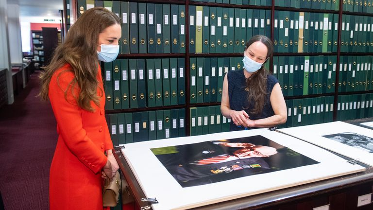 The Duchess of Cambridge views a photo of Captain Tom Moore alongside Curator Magda Keaney during a visit to the archive in the National Portrait Gallery in central London to mark the publication of the 'Hold Still' book. Picture date: Friday May 7, 2021.