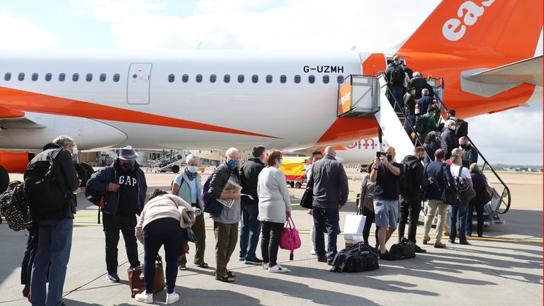 Passengers prepare to board an easyJet flight to Faro, Portugal, at Gatwick Airport in West Sussex after the ban on international leisure travel ends