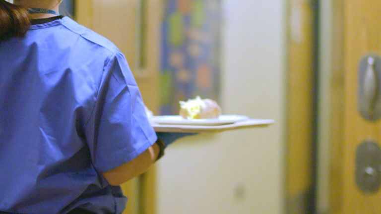 Nursing assistant Emily Heap takes a meal to a patient