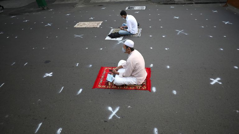 Muslim men sit among physical distancing markers during an Eid al-Fitr prayer marking the end of the holy fasting month of Ramadan on a street in Jakarta. Pic: AP
