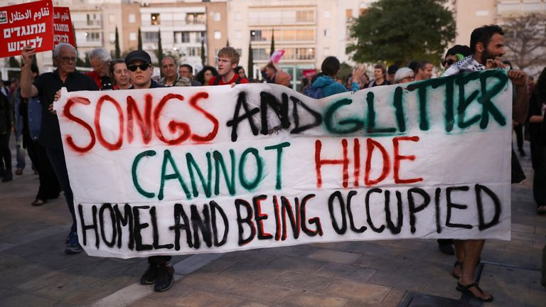 FILE - In this Tuesday, May 14, 2019 file photo, peace activists call for lifting the Gaza blockade and to boycott the ongloing Eurovision Song Contest in Tel Aviv, Israel. The Eurovision Song Contest has always been a sign of its times. Despite the cancellation of the wildly popular contest in Europe and beyond, the evening the finale on Saturday, May 16, 2020 will bring some respite for diehards, with a remote television show beamed to over 40 nations. (AP Photo/Oded Balilty, file)