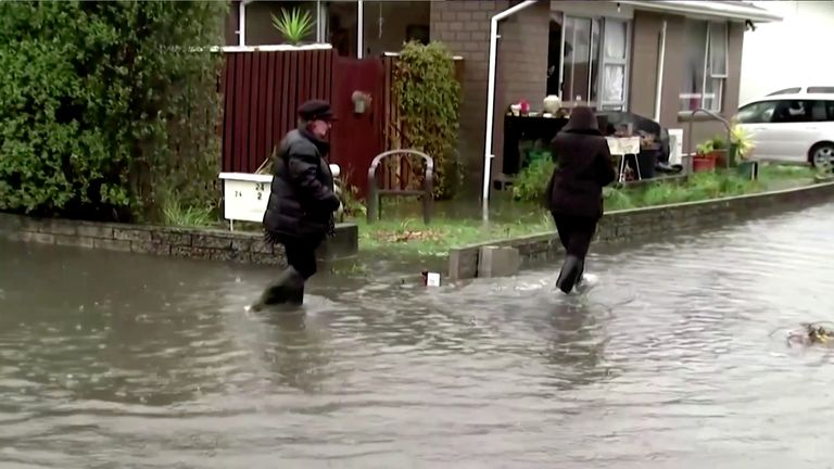 People wade through floodwaters in Canterbury, New Zealand, May 30, 2021, in this still image obtained from a video. TVNZ/via Reuters