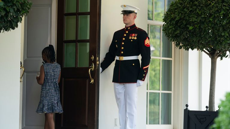A Marine holds the door as Gianna Floyd, the daughter of George Floyd, walks into the White House Pic: AP