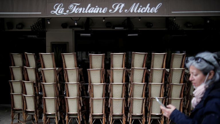 A woman walks past a closed restaurant with piled up chairs during preparations for the reopenning of restaurants and bars in Paris as part of an easing of the country's lockdown restrictions amid the coronavirus disease (COVID-19) outbreak in France, May 18, 2021