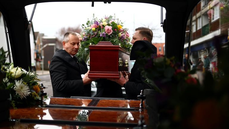 Pallbearers from W. Uden & Sons Family Funeral Directors load a coffin into a hearse ahead of a funeral service in Bromley, amid the coronavirus disease (COVID-19) pandemic, in south east London, Britain, January 28, 2021. Picture taken January 28, 2021. REUTERS/Hannah McKay