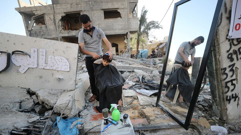 A barber works amid rubble of his shop, which was destroyed in an Israeli airstrike during Israeli-Palestinian fighting, in Gaza City May 25, 2021. REUTERS/Mohammed Salem