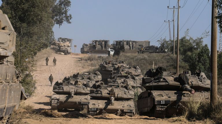 Israeli soldiers assemble with their tanks at the Gaza border